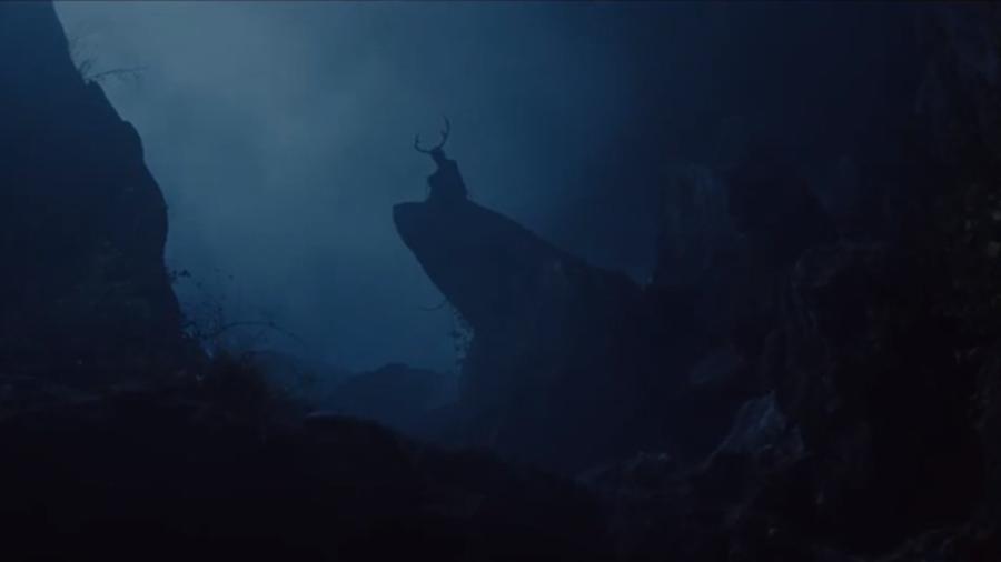 Dans la nuit se détache la silhouette d'un homme avec une paire de bois sur la tête.